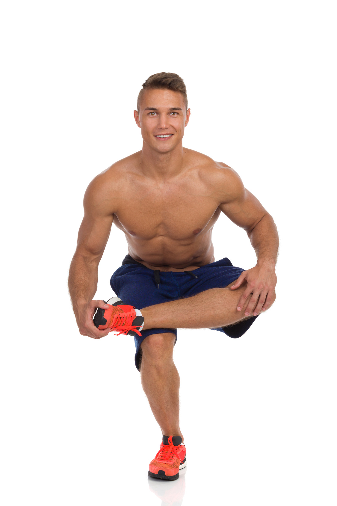 Young fit man in blue shorts and orange sneakers crouching on one leg, holding his leg on other leg knee and stretching gluteus maximus. Front view. Full length studio shot isolated on white.